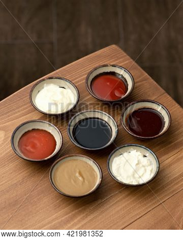 Set Of Different Multi-colored Sauces In Crockery On Wooden Table. Variety Of Sauces, Mayonnaise, Mu