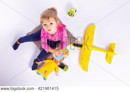 Lovely Babygirl, Toddler Wearing Pink Blouse And Blue Pants, Long Ponytail, Blonde Hair, Sitting On