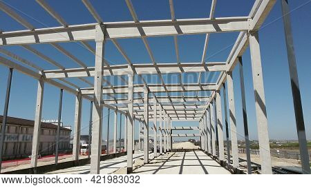 Reinforced Concrete Frame Of An Industrial Building. Camera Flight On A Construction Site. Beams Wit