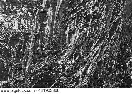 Black Glued Crumpled Shiny Grunge Plastic. Wrinkled Polyethylene Film. Abstract Background