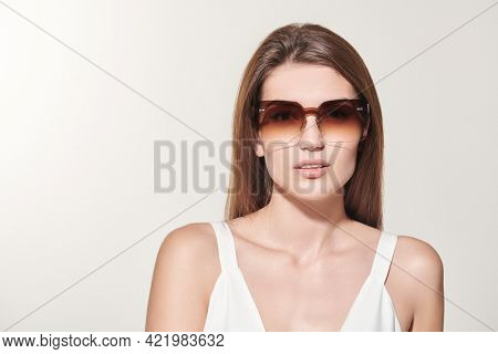 Summer fashion, clothes and accessories. Portrait of a beautiful brown-haired girl in a white summer dress and fashionable sunglasses on a white background. Copy space.