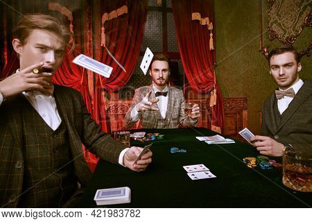 A gambler throws cards over a gambling table in a casino. Handsome rich men spending time in the casino. Luxury lifestyle.