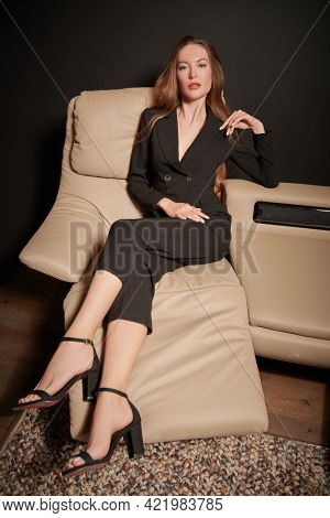 Luxury lifestyle. Attractive glamorous girl in black suit sits on a leather sofa in modern apartments. Fashion. Modern interior, furniture.