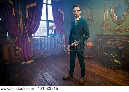 Handsome and respectable man. Full length portrait of a handsome man in elegant classic suit standing with his walking stick in a luxury apartment. Men's beauty, fashion.