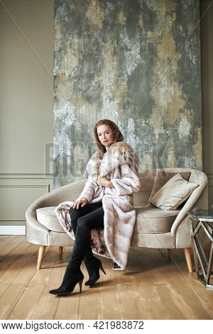 Fur coat fashion. Beautiful blonde woman in an expensive mink and lynx fur coat posing in an apartment with a classic luxury interior.