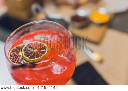 Making Tequila Sunrise Cocktail. Grenadine Slowly Poured Into A Glass Of Ice, Orange Juice And Tequi