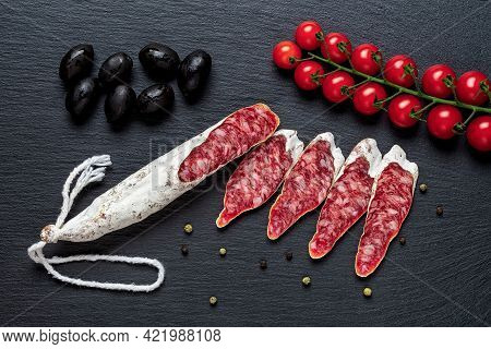 Slices Of Fuet Catalan Thin Sausage, Black Olives And Cherry Tomatoes On The Vine Over Black Slate S
