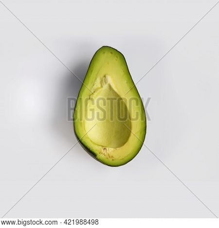 Half A Pitted Green Ripe Avocado Isolated On Light-gray Background. Flat Lay, Top View