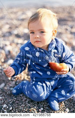 Little Kid In A Blue Overalls Sits On A Pebble Beach, Clutching An Apple In His Hand. Close-up