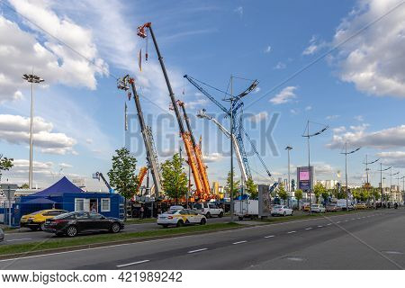 Extended Telescopic Booms Of Mobile Cranes And Telescopic Lifting Cradles At An Open Exhibition Area