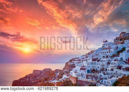 Scenic sunset over sea and picturesque Oia town on Santorini island in summer. Oia, Santorini, Greece