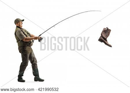 Full length profile shot of a mature fisherman catching an old boot with a fishing rod isolated on white background