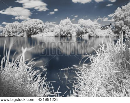 Near infrared photography of beautiful summer river bank and cloudy sky. Picture was taken with infrared-pass filter.