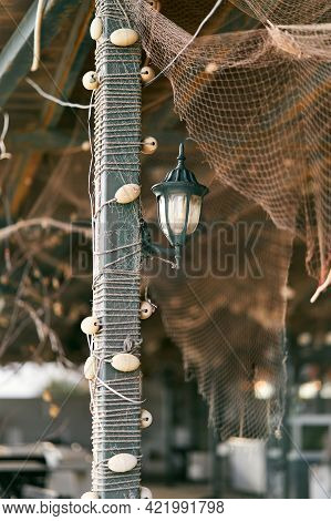Lantern Hangs On A Pillar Braided With Fishing Tackle Under A Canopy With A Fishing Net