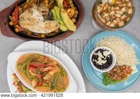 Mexican Food Feast With A Variety Of Seafood Fish, Shrimp, And Shellfish With Rice And Beans As Side