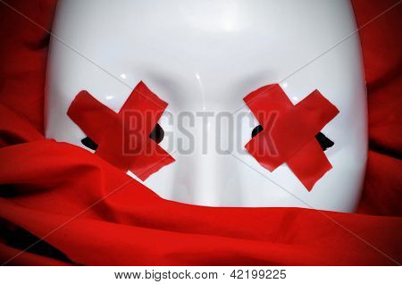 white mask with red tape strips forming crosses in its eyes on a red fabric background