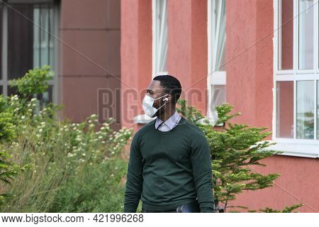 Young Man Of African American Appearance In A Medical Mask On The Street. High Quality Photo