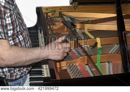 A Tuner Tuning A Grand Piano With Special Ratchet, Indoor Closeup