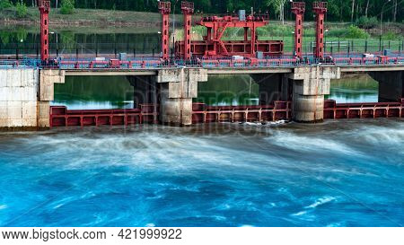 River, Dam, Bridge. Car And Pedestrian Bridge In The Morning. A Full-flowing River With A Strong Cur