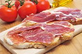 pa amb tomaquet, slices of bread with tomato, with spanish serrano ham served as tapas poster