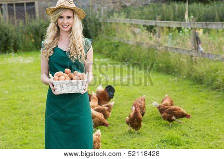 Young woman presenting a basket filled with eggs with chickens behind her