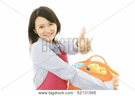 Pretty Asian woman carrying laundry basket