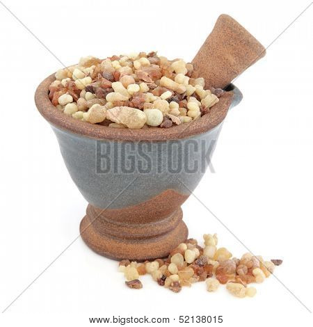 Frankincense and myrrh in a mortar with pestle over white background.