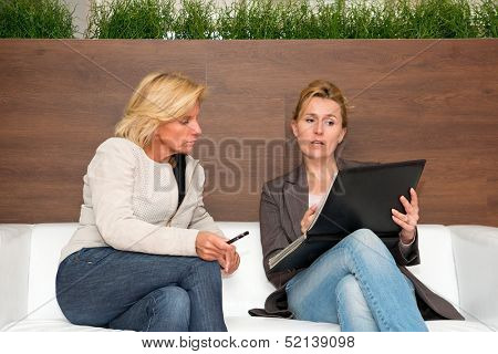 Sales woman showing a product portfolio to a prospect - a senior executive, looking doubtful, both sitting on a white couch in a modern office space