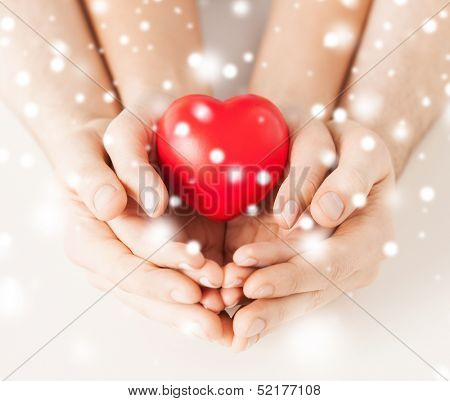 family, charity, healthcare, health. christmas, x-mas and happy people concept - woman and man hands with heart poster
