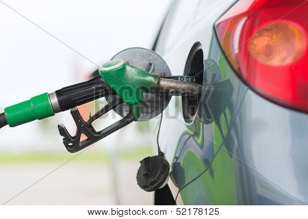 transportation and ownership concept - pumping gasoline fuel in car at gas station poster