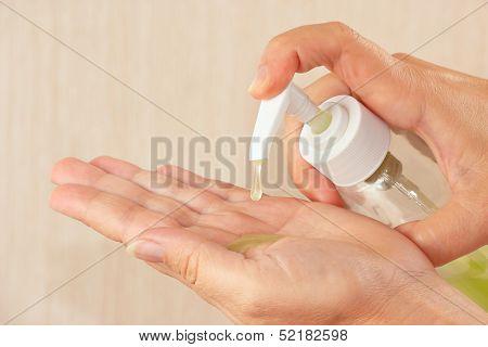 Female hands applying antibacterial liquid soap