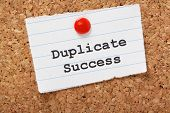 Duplicate Success typed onto a scrap of lined paper and pinned to a cork notice board. In business we search for best practices that produce the results we want and then try to build on the success. poster