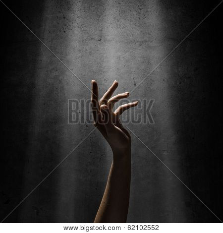 woman's hand reaches for the light rays