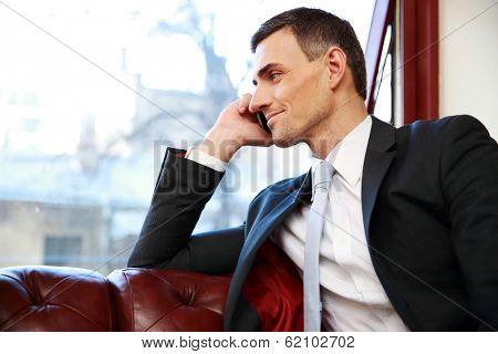 Smiling businessman talking on the phone and looking in window at office