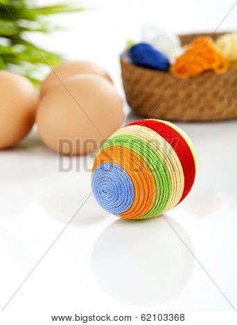 Easter egg covered with woolen yarn. Some eggs, wicker basket filled with colorful wool and green grass in background.