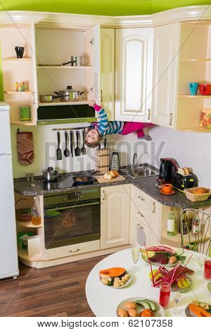 Little girl upside down holds a shelves in the kitchen with table and dishes