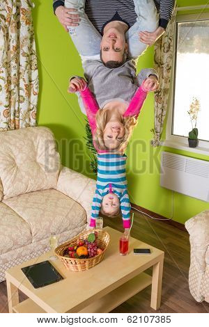Family of three upside down on green room at inverted house