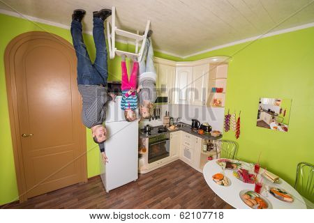 Family of three upside down in the kitchen with table and fridge