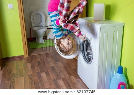 Girl with shirt upside down holding a washing machine at inverted house
