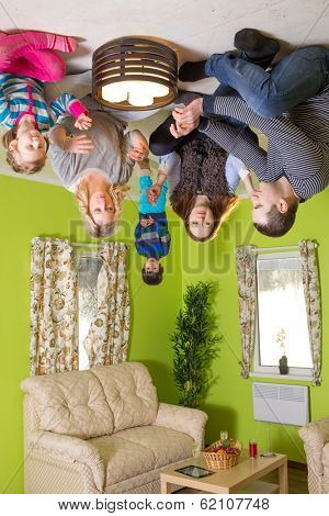 Family of five sits on the ceiling upside down with candles at inverted house