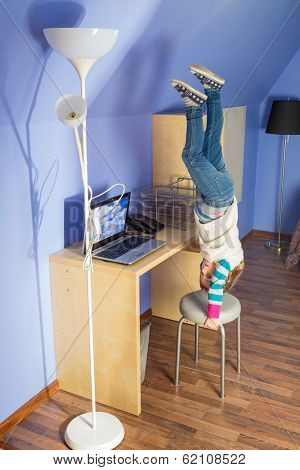 Little girl in jeans upside down on the chair at inverted house