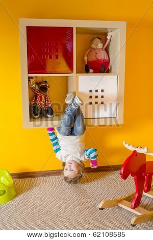 Little girl in children room sitting upside down at inverted house