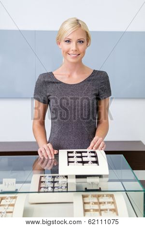 Shop assistant at the window case with rings at jeweler's shop. Concept of wealth and luxurious life