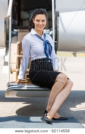 Full length portrait of beautiful airhostess sitting on ladder of private jet