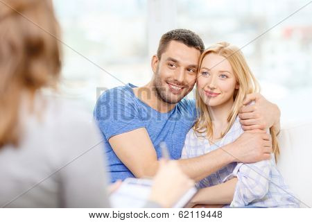 love, family, phychology and happiness concept - young couple hugging at psychologist office