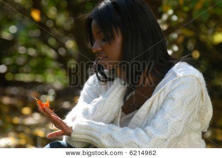 African-american Woman Gazes At A Leaf