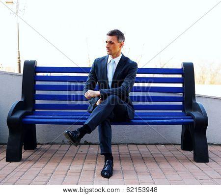 Portrait of a businessman sitting on bench