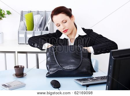 Beautiful business woman is looking for something in her handbag in office.