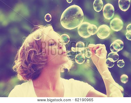 a pretty girl blowing bubbles - vintage toned with a retro instagram filter