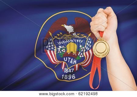 Sportsman holding gold medal with State of Utah flag on background. Part of a series. poster